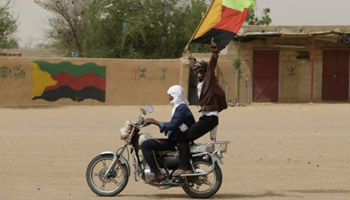 Un Touareg agite le drapeau du Mouvement national de Libération de l'Azawad (MNLA) à Kidal. Photo AFP