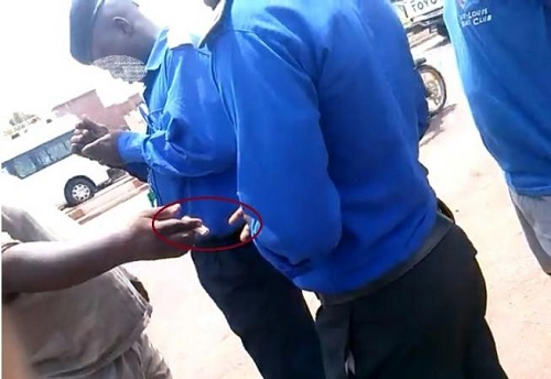 Un scène de corruption flagrante au grand marché de Bamako. L'usager tend un billet à l'Agent de Police. Crédit photo Malijet